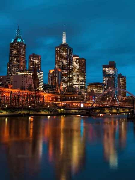Großstadt mit beleuchteten Wolkenkratzern bei Nacht am Fluß mit Brücke